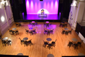 Socially distanced tables laid out in front of the Derby Hall stage at The Met
