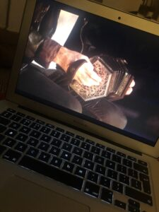 Close-up shot of an accordian being played visible on a laptop screen.